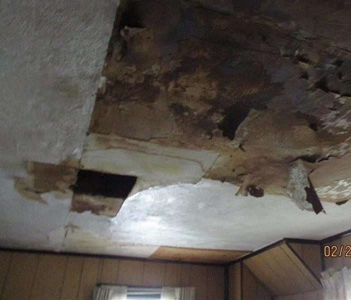 A hole in the ceiling caused by powerful winds from a storm.