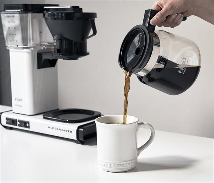 A picture of some pouring a cup of coffee with a coffee maker in the back ground on a white counter top.